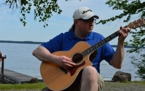 Aaron Mittler playing guitar in front of the Great Sacandaga Lake
